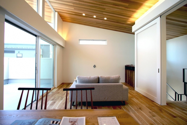 庇と天井にウッドパネルを貼り一体感を出し空間を広く演出