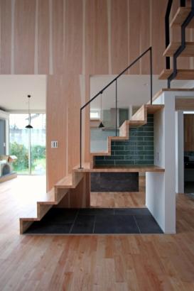 ガラスのリビングドアから入るとリビング中央にある綺麗な階段が鎮座します。