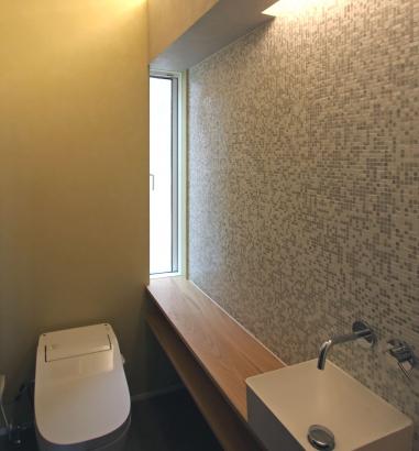 山桜の無垢材をカウンターに使用し、その上の壁は一面モザイクタイルで仕上げた美しいトイレ